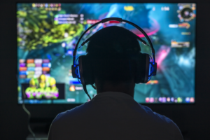 Boy with headphones on playing a game on a large screen